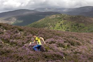 Running across the purple heather in the Scottish Highlands in an adventure sport